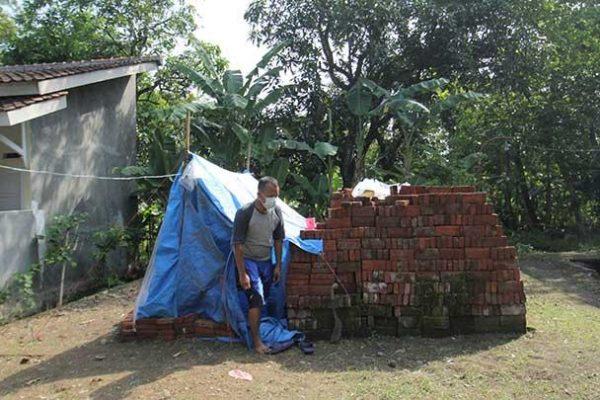 Seorang warga terkonfirmasi positif COVID-19 berada di sekitar tenda terpal untuk menjalani isolasi mandiri di desa Lohbener, Indramayu, Jawa Barat, Rabu, 30 Juni 2021. Warga tersebut terpaksa menjalani isolasi mandiri dengan membuat tenda dari terpal di pekarangan untuk mengurangi resiko penularan COVID-19 lingkungan keluarga dan tetangganya. ANTARA FOTO/Dedhez Anggara